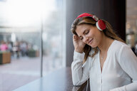 Smiling young woman listening to music with headphones - DIGF04651