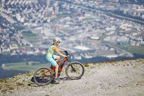 Austria, Tyrol, Woman mountain biking at Patscherkofel, Innsbruck in background - CVF00784