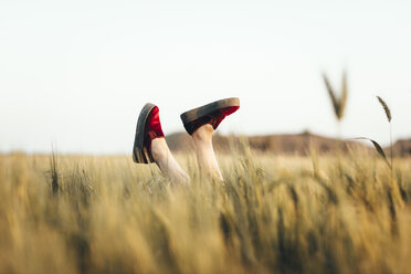 Woman lying in cornfield, kicking legs with red shoes - OCAF00285