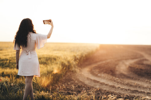 Young woman standing by field, taking selfie at sunset - OCAF00288