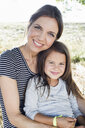 Portrait of mature woman and daughter sitting in park - CUF29087