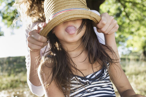 Mature woman covering daughters eyes with  straw hat in park - CUF29093