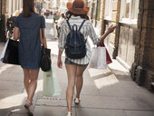 Rear view of two women carrying shopping bags on city street - CUF29132