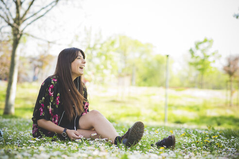 Young woman sitting on park grass listening to earphones - CUF29138