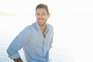 Portrait of happy young man at sunlit lake - CUF29234