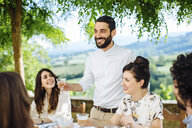 Group of friends having meal together, outdoors, man holding champagne glass, making toast - CUF29318