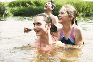 Two sisters and friend swimming in rural lake - CUF29339