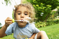 Close up portrait of cute girl blowing bubbles in garden - CUF29342