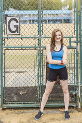Young woman standing beside sports ground, London, UK - CUF29348