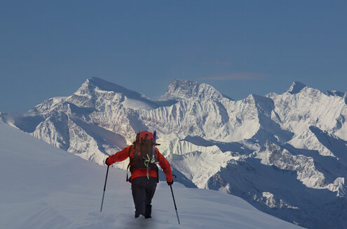 Rear view of climber moving up through deep snow, Swiss Alps, Canton Wallis, Switzerland - CUF29393