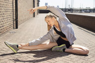 Runner stretching on walkway, Wapping, London - CUF29411