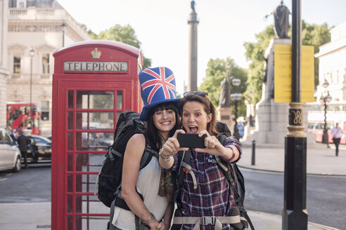 Two women backpackers taking smartphone selfie at red telephone box, London, UK - CUF29435