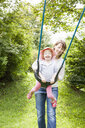 Mother and female toddler playing on park swing - CUF29444