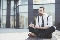 Stylish businessman sitting cross legged making diary notes from smartphone outside office - CUF29477