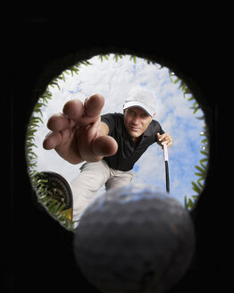 View through hole of golfer reaching for golf ball - CUF29498