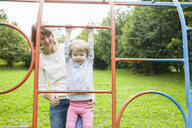 Mother and female toddler playing on park climbing frame - CUF29504