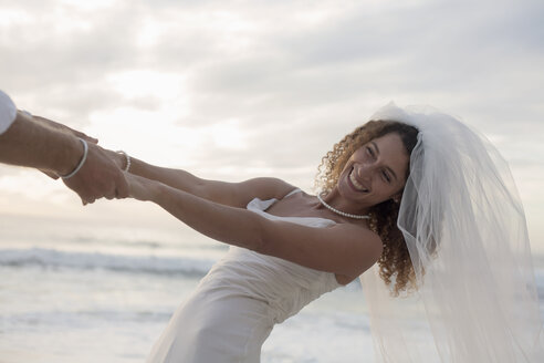 Bride and groom on beach, holding hands, fooling around, laughing - CUF29711