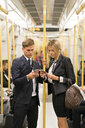 Businessman and businesswoman texting, London Underground, UK - CUF29753