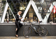 Businesswoman with bike outside 30 St Mary Axe, London, UK - CUF29777