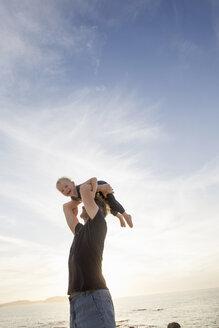 Mature man lifting up his toddler daughter on beach, Calvi, Corsica, France - CUF29837