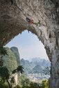Male climber climbing the route Lunatic on Moon Hill in Yangshuo, Guangxi Zhuang, China - CUF29858