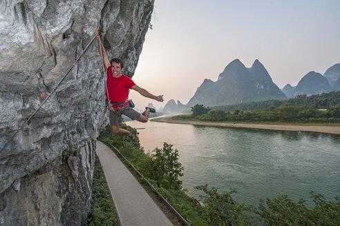 Portrait of male climber hanging off Riverside crag in Yangshuo, Guangxi Zhuang, China - CUF29864