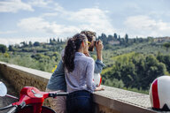 Young couple photographing view of hills, Florence, Italy - CUF29876