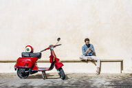 Young male moped rider sitting on bench reading smartphone texts, Florence, Italy - CUF29882