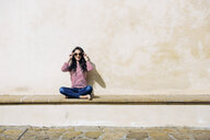 Portrait of young woman adjusting sunglasses on bench, Florence, Italy - CUF29888