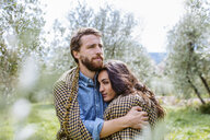 Young romantic couple wrapped in blanket in olive grove, Florence, Italy - CUF29891