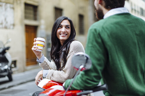 Young couple leaning on moped with takeaway coffee, Florence, Italy - CUF29897