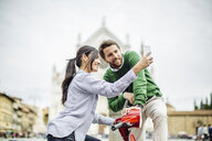 Young couple on moped taking smartphone selfie in front of Basilica di Santa Croce, Florence, Italy - CUF29900