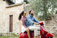 Side view of young couple riding moped in village, Florence, Italy - CUF29906