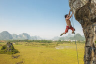Male climber hanging from the Egg - a lime stone cliff in Yangshuo, Guangxi Zhuang, China - CUF29951