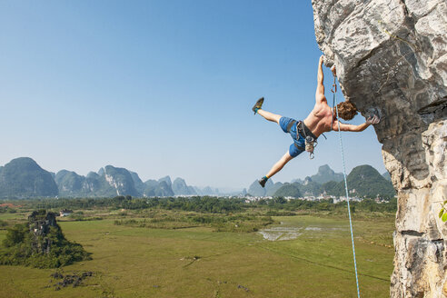 Male climber hanging from the Egg - a limestone cliff in Yangshuo, Guangxi Zhuang, China - CUF29954