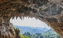 Female climber climbing Odin's Dan - a limestone cliff in Yangshuo, Guangxi Zhuang, China - CUF29957