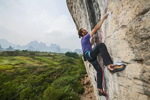 Male climber climbing at white Mountain - a limestone cliff in Yangshuo, Guangxi Zhuang, China - CUF29960