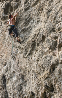 Male climber climbing at white Mountain - a limestone cliff in Yangshuo, Guangxi Zhuang, China - CUF29963