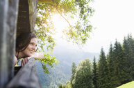 Side view of mid adult woman looking out of treehouse at view, Tegernsee, Germany - CUF29966