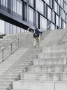 Urban cyclist carrying bicycle ascending stairway - CUF29975