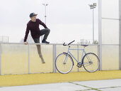 Urban cyclist climbing over fence on sports field - CUF29978