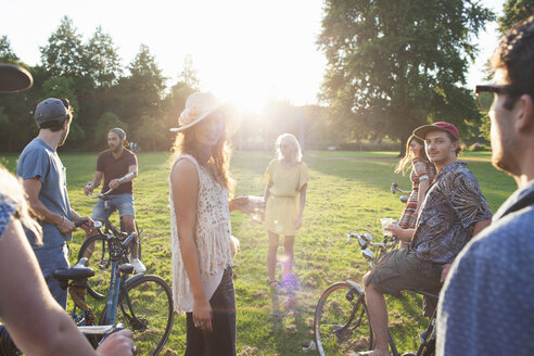 Group of party going adults arriving in park on bicycles at sunset - CUF29999