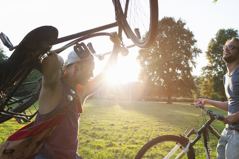 Two male friends arriving in park with bicycles at sunset - CUF30002