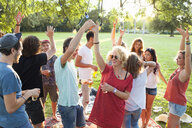 Crowd of adult friends dancing at party in park at sunset - CUF30005