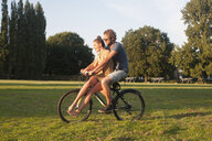 Romantic young couple on bicycle together in park - CUF30032