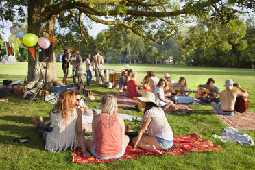 Group of friends listening to music under park tree at sunset  party - CUF30050