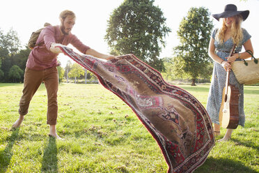 Romantic young couple spreading rug for picnic in park - CUF30059