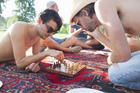 Two young men playing board game at sunset park party - CUF30065