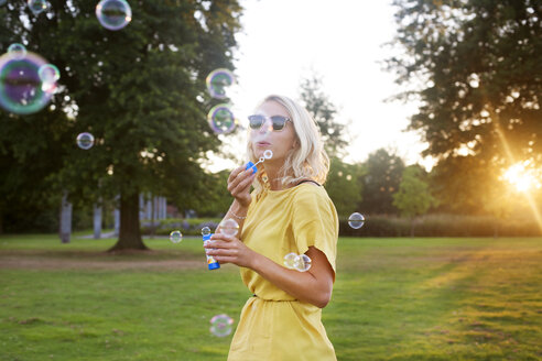 Portrait of young woman wearing yellow dress blowing bubbles in park at sunset - CUF30077