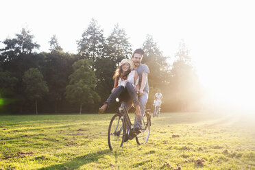 Young woman on handlebars of boyfriends bicycle at party in park - CUF30080